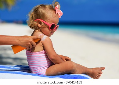 mother applying sunblock cream on daughter shoulder