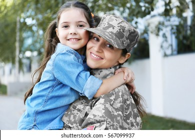 Mother in army uniform and daughter in the street