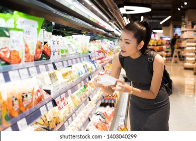 Mother Asian Working woman select pick up healthy nutrition food, yogurt milk from supermarket shelf rack after work. Concept decision Making choice select best thing for kid children family