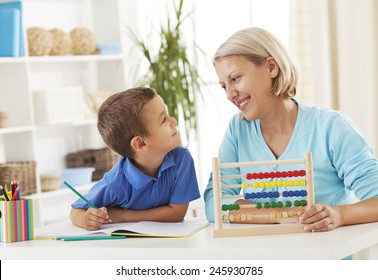 Mother assisting her son to count using an abacus