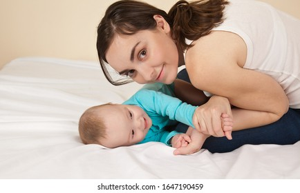 Mother with baby in blue bodysuit playing in bed and having fun