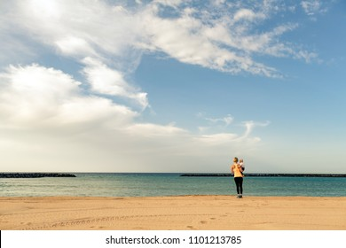 Mother with baby boy enjoy sunrise on a beach. Walking and relaxing woman holding baby boy toddler. Beautiful inspirational beach and ocean landscape.