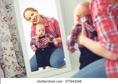mother and baby boy look in mirror and smile at home