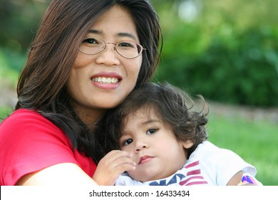 Mother and baby boy sitting on lawn