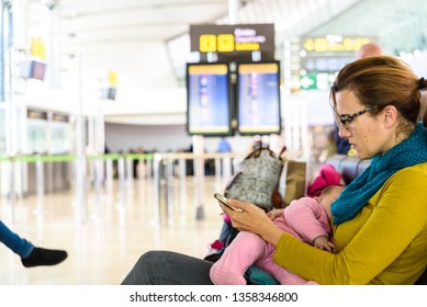 Mother and baby breastfeeding in waiting room of an airport before taking their plane during a trip.