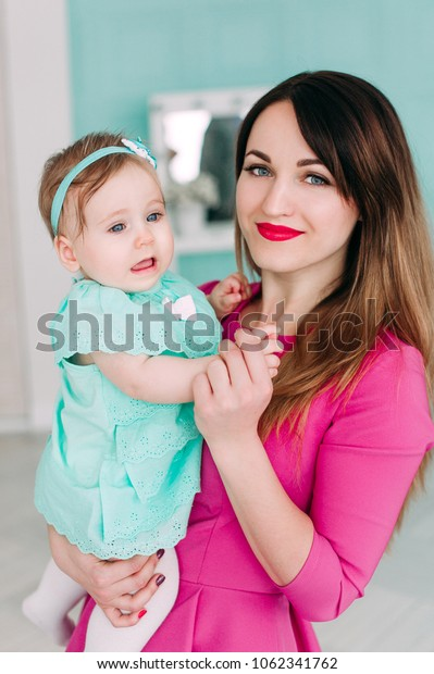 Mother and baby closeup portrait, happy faces, european family picture, adorable small girl, mom and kid having fun indoor, parents joy, holding little child,