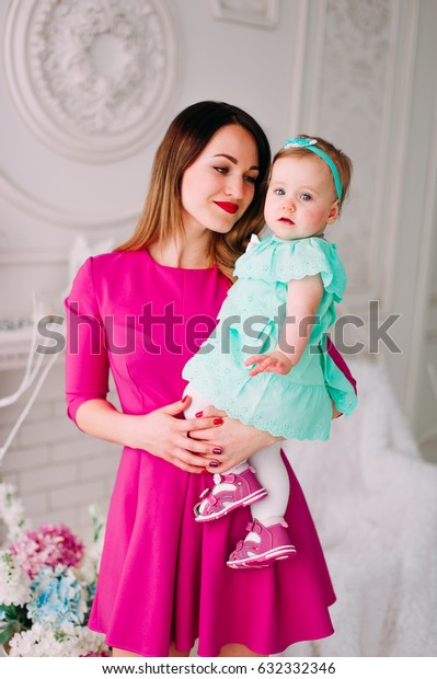 Mother and baby closeup portrait, happy faces, european family picture, adorable small girl, mom and kid having fun indoor, parents joy, holding little child, , happiness concept