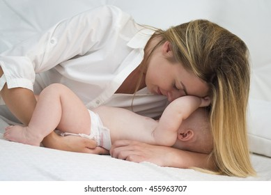 Mother and baby daughter on bed