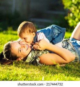 Mother and baby daughter are playing outdoors. Young mom and her cute little baby-girl are having fun in the sunny garden. Happy childhood and parenthood concept.