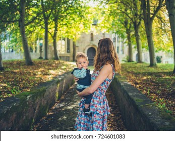 A mother and baby dressed for a formal event are outside a church