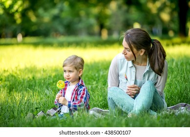Mother and baby eating candy in the park in the summer. Cheerful kid in the summer in the park eating candy. Candy on a stick in a child.