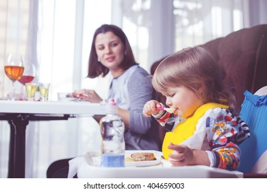 Mother with baby eating in a restaurant
