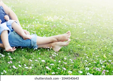 Mother and baby Feet in grass on meadow/ summer relax concept
