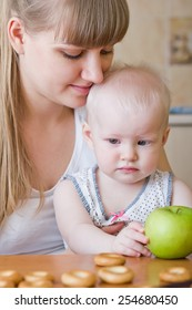 Mother and baby girl with green apple