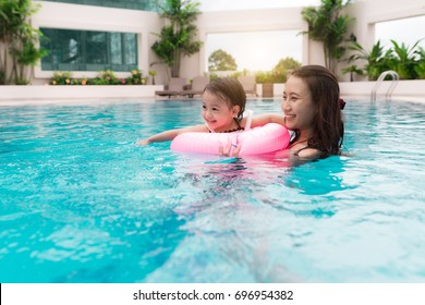 Mother and baby girl having fun in the pool. Summer holidays and vacation concept
