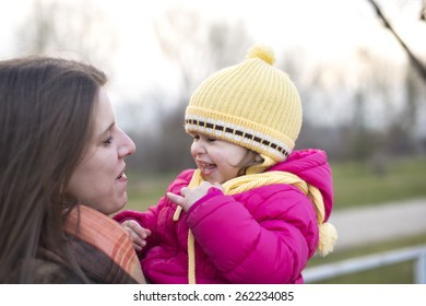 mother and baby girl laughing in the park in winter