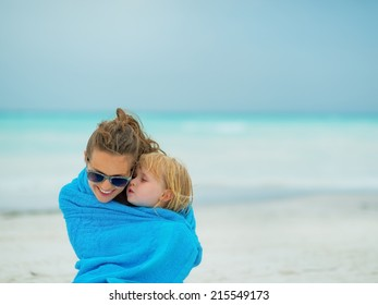 Mother and baby girl wrapped in towel sitting on beach