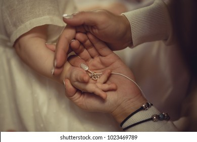 Mother and baby hands with cross