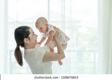 Mother and baby happily tease each other on a white bedroom - mom and baby concept
