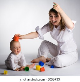 Mother and baby having fun with colorful toys
