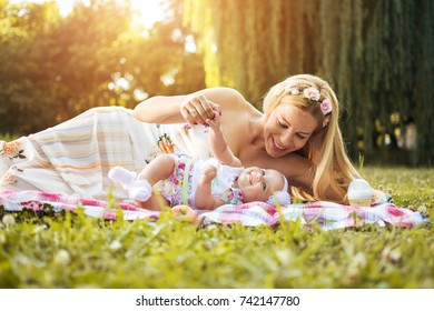 Mother and baby having fun while lying down together on picnic blanket outdoors.