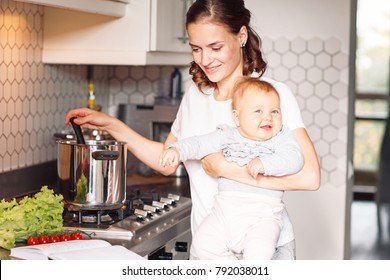 Mother with baby in kitchen. Multifunctional concept