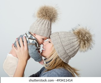 Mother and baby in knitted cap playing and smiling. Happy family.Winter season.