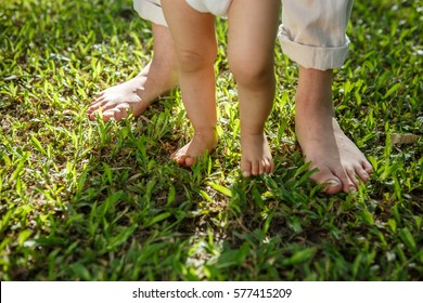 Mother and baby legs walking on the grass, First steps walking is one of the first major steps child