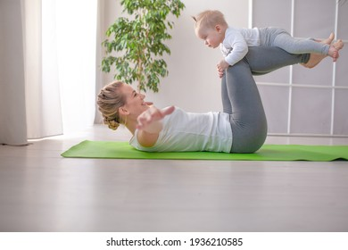 Mother with baby make yoga at home to be strong and healthy