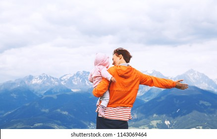 Mother and baby with mountains on a background. Family spend summer holiday in Dolomites, Italy, Europe. View of Bruneck and Pustertal from the summit of Kronplatz.