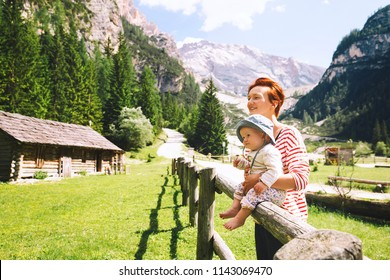 Mother and baby with mountains on a background. Family spend summer holiday in Dolomites, South Tyrol, Italy, Europe. Woman and child on nature in the countryside in the Alpine village