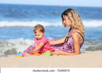 mother with baby on the shore of the sea