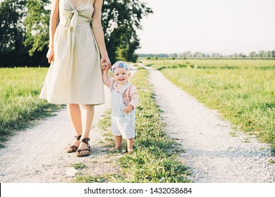 Mother and baby outdoors. Family on nature. Loving woman with child in countryside. Photo of natural parenthood, maternity leave. Theme of zero waste, slow fashion and conscious life, eco lifestyle