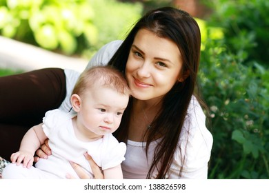Mother with baby at outdoors in green park. Focus on woman