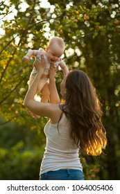 Mother and baby outdoors having fun. Mother holding baby on her arms