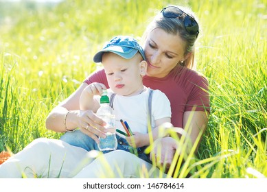 Mother and baby in park portrait. Mother and baby in park portrait. Beautiful young mother with a child in nature. Family resting on the air even somother.