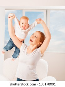 Mother and baby are playing active games, do gymnastics and laughing at home against the window and the sky