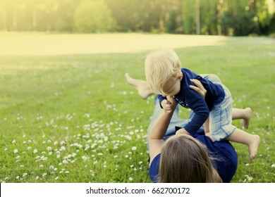 Mother and baby playing on the grass/ summer background with mum and child