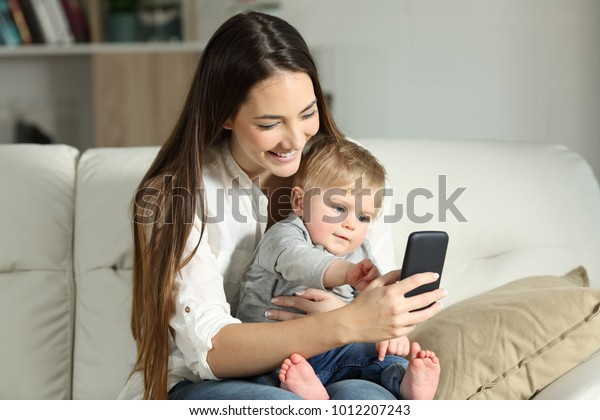 Mother and baby playing with a smart phone sitting on a couch in the living room at home
