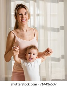 Mother and baby playing and smiling. Happy family. Home interior.