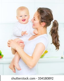 Mother and Baby playing and smiling together. Love. Happy cheerful family Mom and Baby girl kissing and hugging at home. Beautiful healthy mother and little daughter. Maternity concept. Parenthood