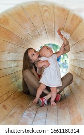 Mother and baby playing in the wooden tunnel on the Eco-friendly playground. Vertical frame.