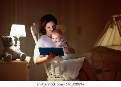 Mother and baby read book in dark bedroom. Mom and child before bed time. Family in the evening. Kids room interior with night lamp and bassinet. Parent holding infant next to crib.