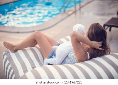 Mother with baby relaxing near luxury swimming pool. Happy harmonious family at first vacation.