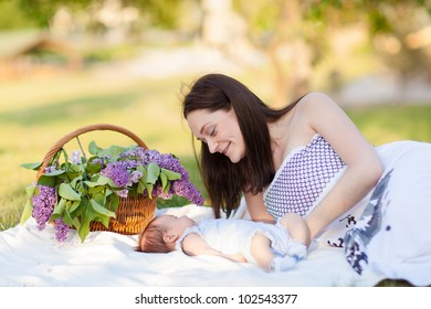 mother and baby resting in summer park