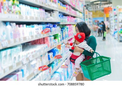 Mother and baby shopping in the supermarket,Thai woman has a daugther