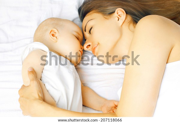 Mother and baby sleep in bed together