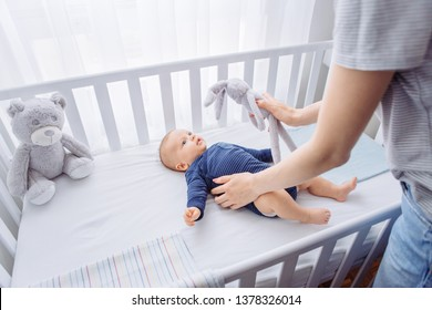 Mother and baby son in bedroom, mother occupy little toddler with stuffed toy