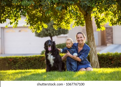 A mother with baby son and black dog in green neighborhood