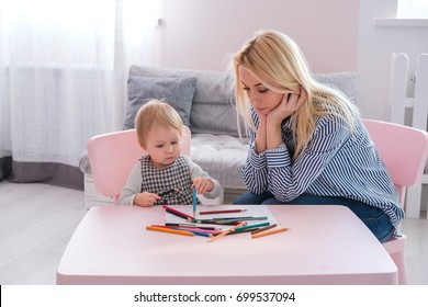 Mother with the baby son with colored pencils